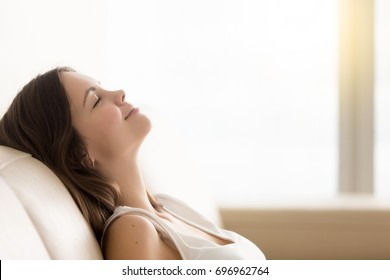 Relaxed young woman enjoying rest on comfortable sofa, calm attractive girl relaxing on couch, breathing fresh air with eyes closed, meditating at home, peace of mind, headshot portrait, copy space - Shutterstock ID 696962764