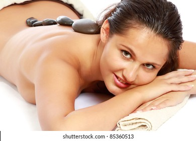 Relaxed young woman getting spa treatment at spa salon isolated