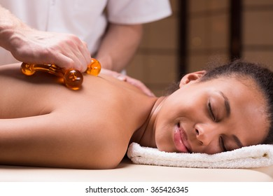 Relaxed young woman having massage with massager