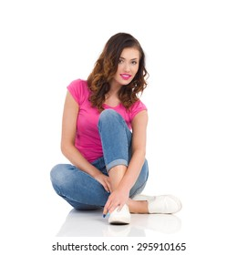 Relaxed young woman in jeans and pink shirt sitting on the floor. Full length studio shot isolated on white.