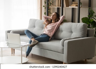 Relaxed young woman leaned on couch closed eyes putting hands behind head enjoy fresh air, freelancer resting from work in modern cozy living room alone, daydream day nap, fall asleep or pause concept