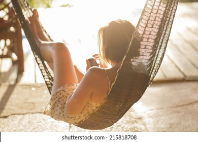 relaxed young woman looking at mobile phone in hammock horizontal