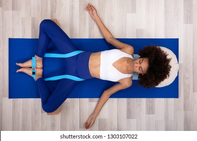 Relaxed Young Woman Lying On Fitness Mat Doing Exercise With Yoga Belt And Two Blocks