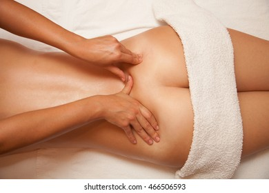 Relaxed young woman lying on her front on a bed receiving a massage on her back by a female therapist