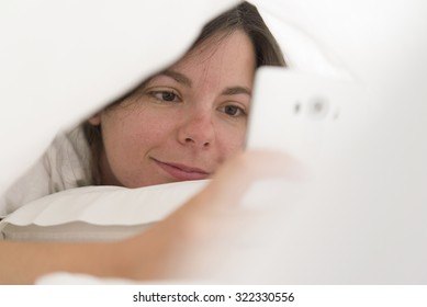 Relaxed young woman with mobile phone lying in bed at home