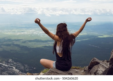 relaxed young woman on top mountain
