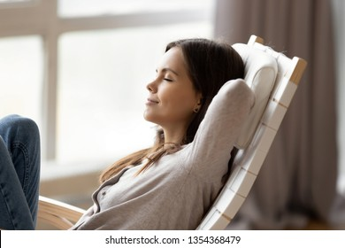Relaxed young woman resting on comfortable rocking chair