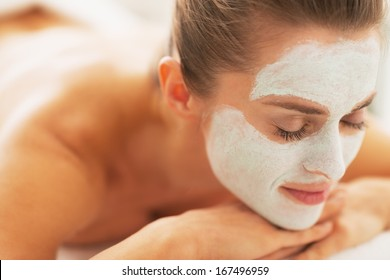 Relaxed young woman with revitalising mask on face laying on massage table
