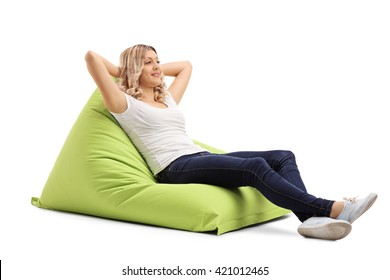 Relaxed young woman sitting on a comfortable green beanbag isolated on white background