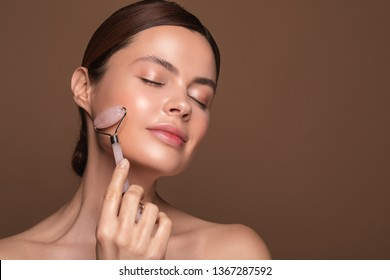 Relaxed young woman standing isolated on the brown background and smiling with closed eyes while using rose quartz face roller