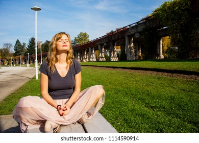 Relaxed young woman taking last sun bath in the middle of autumn sitting in the park