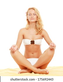 Relaxed young woman in white bikini doing yoga exercise isolated