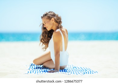 relaxed young woman in white swimsuit on the ocean shore siting on a striped towel. quiet vacation heaven. getting vitamin D after long winter months. carefree beach fun. minimal to no crowd peace.