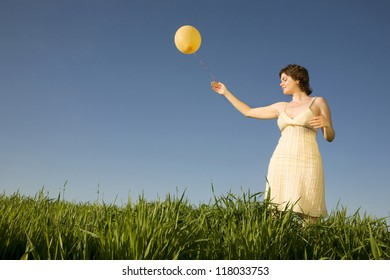 Relaxed young woman with yellow balloon on the field