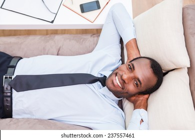Relaxing after long day working. Top view of handsome young African man in shirt and tie holding hands behind head and smiling while lying on the couch
