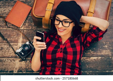 Relaxing after long trip. Top view of beautiful young woman in headwear lying on the floor holding mobile phone and smiling