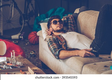 Relaxing after party. Young handsome man in sunglasses lying down on sofa with joystick in his hand in messy room after party
