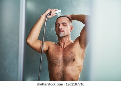 Relaxing after stressful day. Waist up portrait of naked muscular gentleman taking shower at home