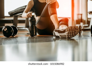Relaxing after training.beautiful young woman looking away while sitting  at gym.young female at gym taking a break from workout.