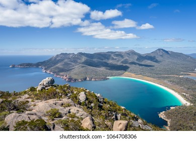 Relaxing amazing mountain viewpoint stunning view to Wineglass Bay sandy beach blue water and enjoyng warm sunny blue sky after hiking on top, Freycinet National Park, Mount Amos, Tasmania, Australia