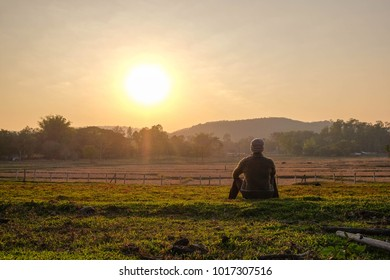 A relaxing Asian man at agriculture field in the morning sunrise.