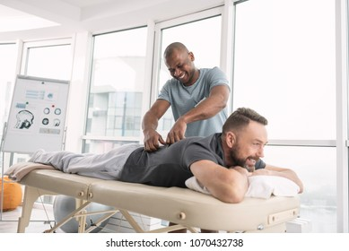 Relaxing atmosphere. Happy delighted man smiling while doing a back massage for his patient