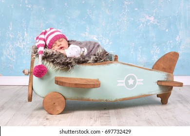 Relaxing Baby Girl on a vintage inspired airplane posing prop.