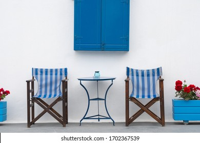 Relaxing balcony of greece taverna. Two blue chair facing the same direction in front of white cement wall and bright blue swing window