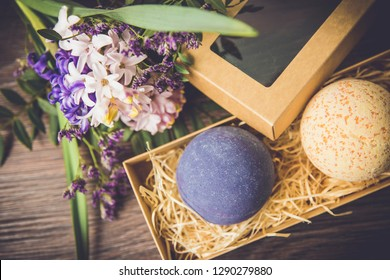 Relaxing bath products for gift present concept. Two colorful bath bombs in a brown cardboard box with decorative pink and purple flower bouquet on the background on wooden table.