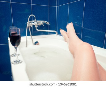 Relaxing in the bathroom with wine glasses