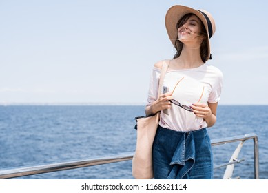 Relaxing beach woman enjoying the summer sun happy standing in a wide sun hat at the beach with face raised to the sunlight. Head and shoulder portrait. Multicultural Caucasian enjoyment in vacation