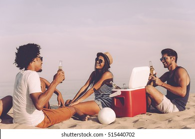 Relaxing with best friends. Cheerful young people spending nice time together while sitting on the beach and drinking beer