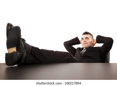 Relaxing business man with feet up on the desk  office, isolated on white