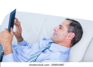 Relaxing businessman on a sofa with a tablet against a white wall
