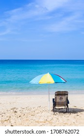 Relaxing by the beautiful beach, holiday and vacation destination to Paradise island in South of Thailand, beach chair under colorful umbrella with blue sea view and clear blue sky
