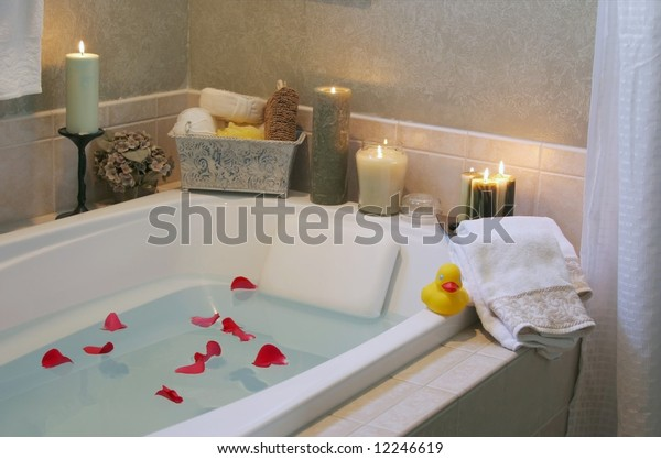 A relaxing candlelit bath with rose petals and a a rubber duck. Low lighting since bathroom was only lit with candles to create relaxing atmosphere.
