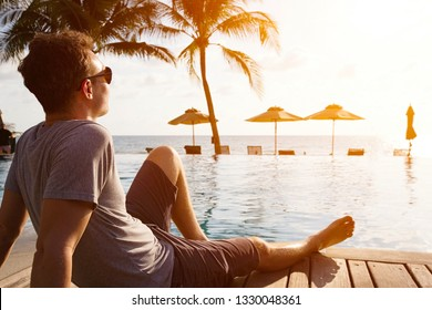 Relaxing caucasian man sitting near luxurious swimming pool with view on beach and sea horizon at sunset. Travel and vacation on tropical island in Thailand. onocean shore hotel with palm trees.