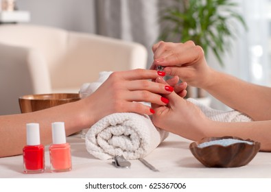 Relaxing day at beauty salon. Manicurist master makes manicure on woman's hand.  Hand care in the spa.
