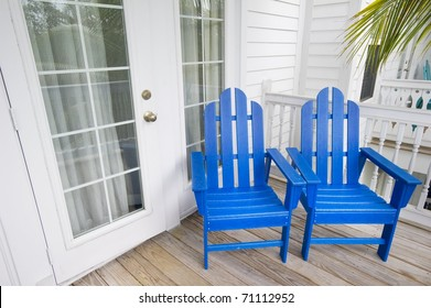 Relaxing depiction of blue Adirondack Chairs in Key West Florida with a palm tree in the background