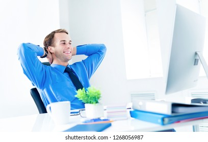 Relaxing or dreaming businessman in blue shirt and tie, with hands behind head, using desktop computer at office. Success in business, job and education concept.