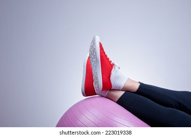 Relaxing with fitness ball, workout, female legs close up