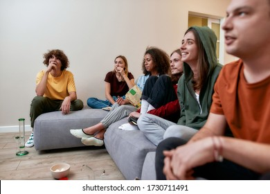 Relaxing with friends. Young multicultural people having fun, eating snacks and talking, sitting on the coach at home. Smoking marijuana from a bong. Home party. Cannabis weed legalization, ganja
