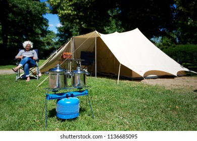 Relaxing in front of tent with gas stove in foreground