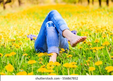 Relaxing girl lying in a blooming meadow in summer sunshine