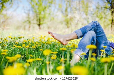 Relaxing girl lying on the spring blooming meadow