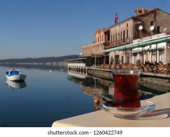 A relaxing glass of Turkish tea with a seaside view from the Aegean town Ayvalik on the background, in Turkey.
