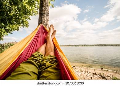 Relaxing in the hammock at the beach under a tree, summer day. Barefoot man laying in hammock, looking on a lake, inspiring landscape
