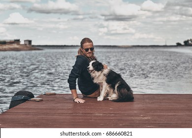 Relaxing with his friend. Handsome young man and his dog sitting near the lake while spending time outdoors