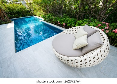 relaxing holiday by swimming pool with clear blue water / Empty sunbeds by the pool