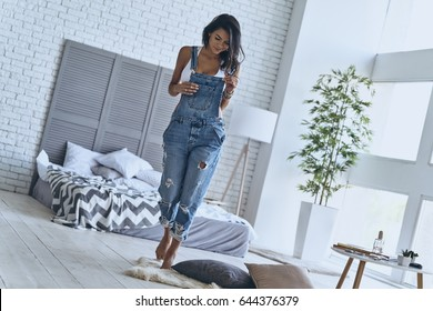 Relaxing at home. Full length of attractive young woman smiling while walking in the bedroom at home